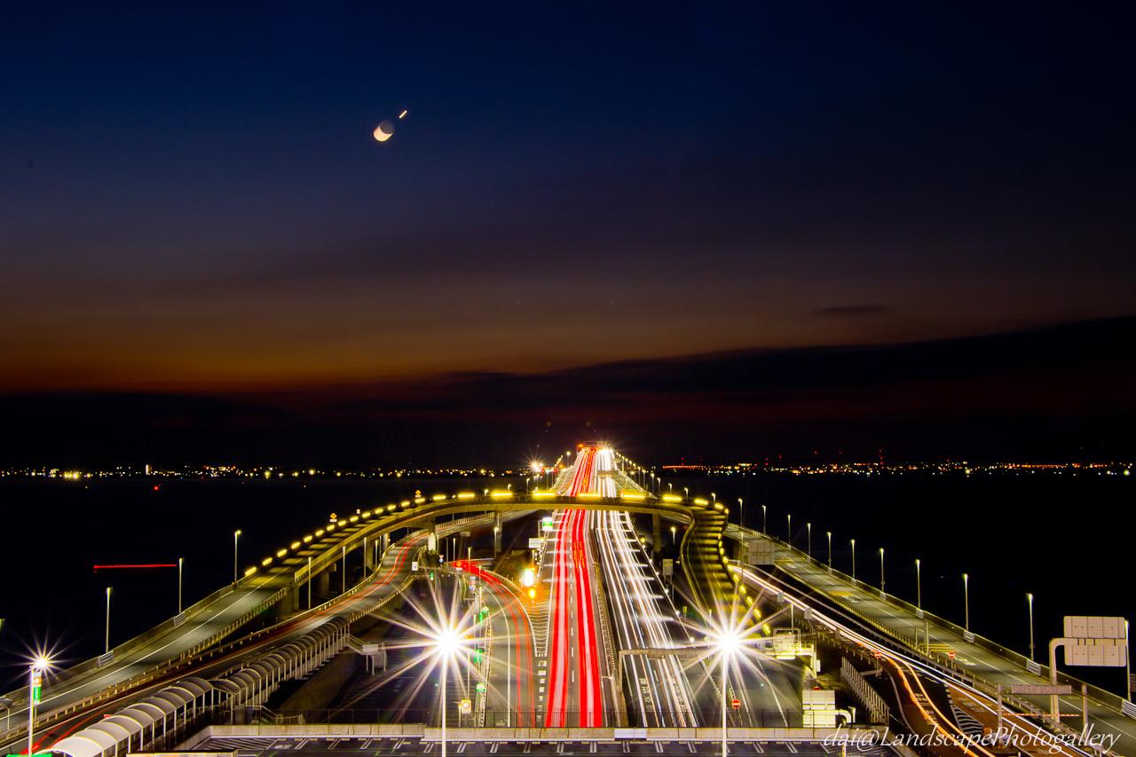 夜明けの東京湾アクアラインの光跡と月と金星