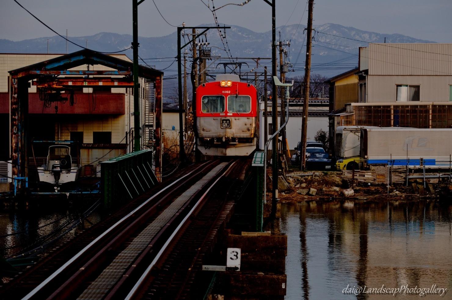 夕刻の北陸鉄道大野川橋梁と残雪の両白山地
